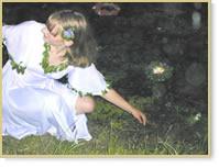 Young woman placing wreath in the water in an  Ivan Kupalo ritual