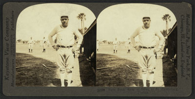 """George Herman """"Babe"""" Ruth, full length, standing, facing front; wearing baseball uniform; in field with hands on hips; other players in background."""
