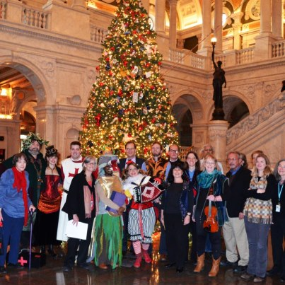 Photo: The American Folklife Center staff, including the AFC Mummers, wish all of our friends a very happy holiday season.  On December 18 and 19, members of the AFC staff presented a mummers play, derived from texts collected in Britain, which are part of AFC's James Madison Carpenter Collection.  One of the venues for the play was the Great Hall of the Library of Congress, next to the Library's Christmas tree.  After the play, the costumed mummers joined the rest of the staff for this group photo.