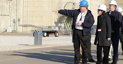 NRC Commissioner Kristine L. Svinicki (center) and NRC Senior Resident Inspector John Kramer (right) listens to Steven Sewell (left), Luminant's director of Organizational Effectiveness, during her tour of the Comanche Peak nuclear power plant near Glen Rose, Texas. The reactor containment building is in the background.