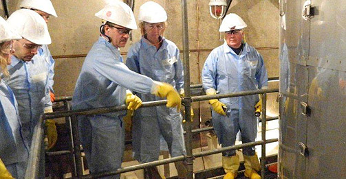 NRC Chairman Allison Macfarlane (second from right) listens as Southern California Edison executive Richard St. Onge (third from right) discusses issues with one of the damaged steam generators at the San Onofre Nuclear Generating Station near San Clemente, Calif. The steam generator is in the right foreground.