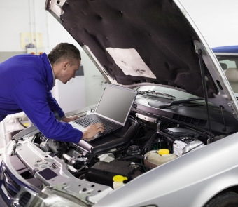 Image of mechanic looking under the hood of a car