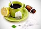 A cup of tea with a slice of lemon and medicine next to it