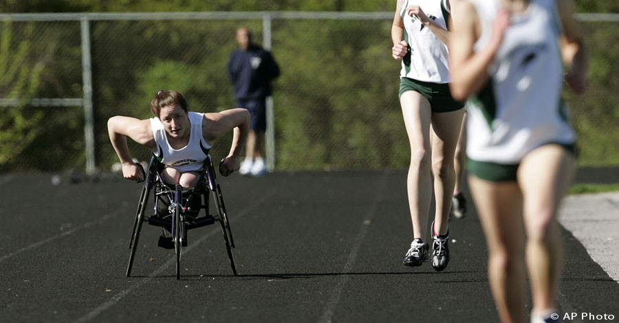 Wheelchair athlete, left, races along side able-bodied high school runners, April 19, 2006 in Rockville, Md. [AP File Photo]