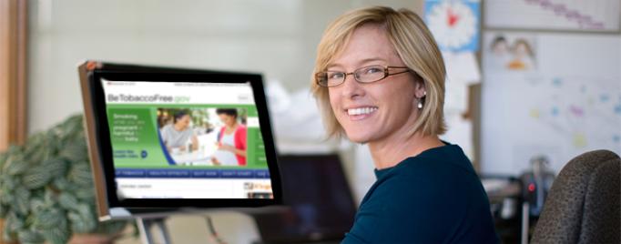 Mujer sentada delante de una pantalla de computadora que muestra el sitio BeTobaccoFree.gov