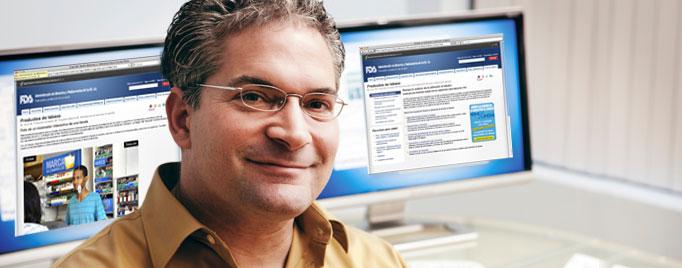 Hombre frente a dos monitores que muestran los sitios de la FDA. Uno en inglés y uno en español.
