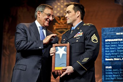 Defense Secretary Leon E. Panetta presents former Army Staff Sgt. Clinton L. Romesha with the Medal of Honor Flag at the Pentagon, Feb. 12, 2013.