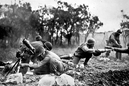 U.S. soldiers pass ammunition as they fire on German troops near Massa, Italy, Nov. 1944. The soldiers are members of an African-American company assigned to the 92nd Division. This company is credited with liquidating several machine gun nests.