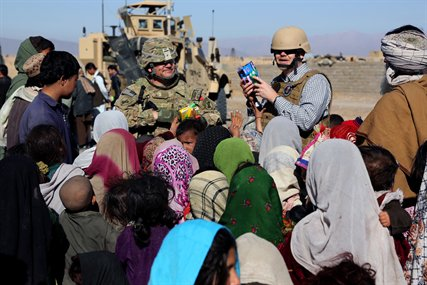 U.S. Army Lt. Col. Mark Martin, left, and Ray Sudweeks, right, U.S. State Department representative, pass out toys and school supplies to Afghan children in a village in Farah province, Afghanistan, Feb. 9, 2013. Martin, a civil affairs officer, is assigned to Provincial Reconstruction Team Farah.