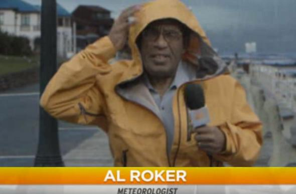 Weatherman Al Roker dressed in foul-weather gear with microphone, standing in a driving rain on the waterfront.