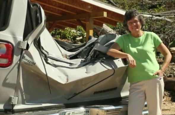 Tornado Survivor Evonne Richards leaning against a wrecked cargo van.