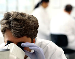 The image displays a photo of a scientist working in a lab