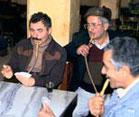 Men seated around table smoking water pipes