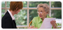 A woman speaking with a senior woman.