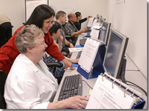 Photo of a classroom instructor leaning over a student assisting with a program on the computer.