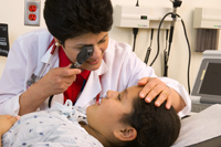 Doctor examining a young girl's eyes