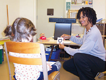 Lady playing an eye card game with a young kid.