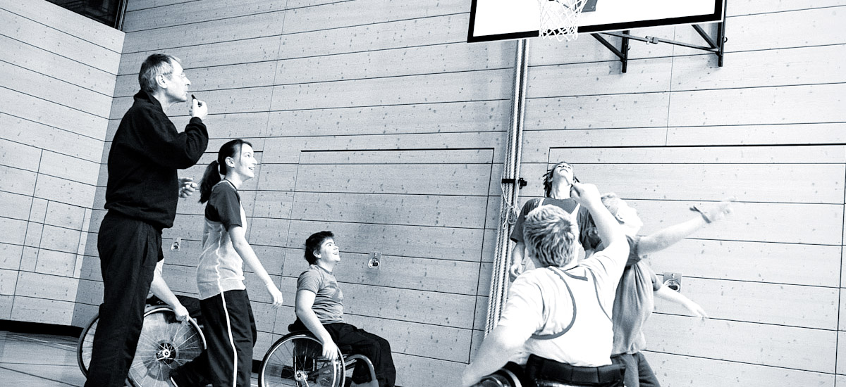 Photo of kids in wheelchairs playing basketball while coach blows whistle
