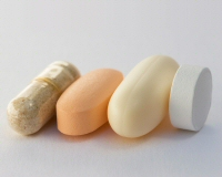 Four generic supplement pills: fiber, multivitamin, fish oil, and garlic.