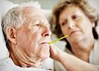 An elderly woman takes an elderly man's temperature