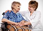 An elderly woman in her wheelchair talks with a nurse