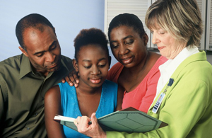 A teenager, her parents and a female doctor standing together. They are looking at information in a book.