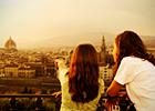 Two women point to European city landscape