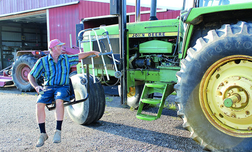 Indiana farmer Mark Hosier, paralyzed from the waist down, uses a mechanical lift to board his tractor.