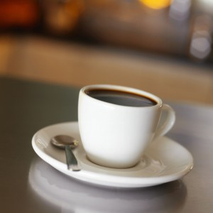 White cup full of coffee with saucer and spoon