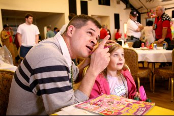Lt. Col. Philip Speth, U.S. Army Space and Missile Defense Command/Army Forces Strategic Command, tells his young customer to look up so that he can paint her design choice on her cheek during the Survivors Outreach Services Mardi Gras at The Overlook, Feb. 9, at Redstone Arsenal, Ala. The event was sponsored by SOS and SMDC.