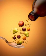 Frutas y nueces echando desde un frasco de vitaminas