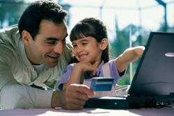 Foto de padre e hija mirando el computador