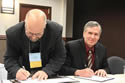 Tim Mattick (left), president of the Montana Grain Elevators Association, signs the alliance documents along with Jeff Funke, director of OSHA's Billing Area Office. View the slideshow for more images and captions.