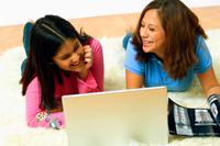 Madre con su hija preadolescente sonriendo frente a una computadora portátil