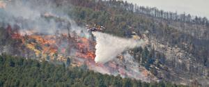 Helicopter spreading water over a forest fire.
