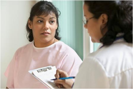 Female health provider with clipboard speaks to female patient
