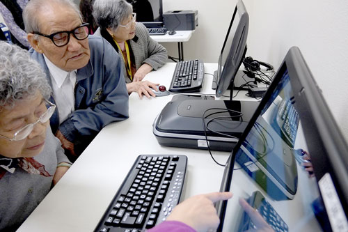 older computer users at a computer receiving help from an instructor