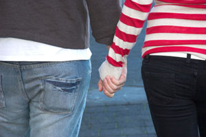 Photograph of two teens holding hands.