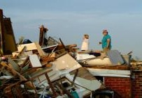 Two women survey the damages to their home after a tornado destroyed the structure