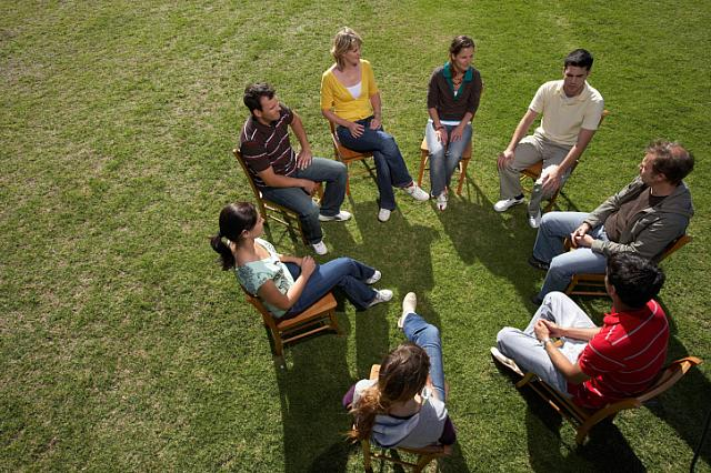 Young people sitting in a circle on the grass.