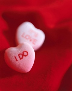 "Photograph of pink candy hearts, on says ""I Do"" the other ""It's Love"""