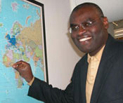 Dr. Clement Adebamowo looks at camera, smiling, points to Nigeria on a world map