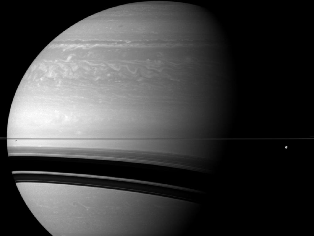 Image description: The Cassini spacecraft took this photo of Saturn in December 2011 from a distance of approximately 1.3 million miles away. The scale of the image is about 77 miles per pixel. Three of Saturn's moons, Tethys, Enceladus, and Pandora,are shown. Tethys is on the right of the image, below the rings. Enceladus is on the left, below the rings. Pandora is barely visible. It appears as a small grey speck above the rings on the extreme left edge of the image. Photo from NASA/JPL-Caltech/Space Science Institute