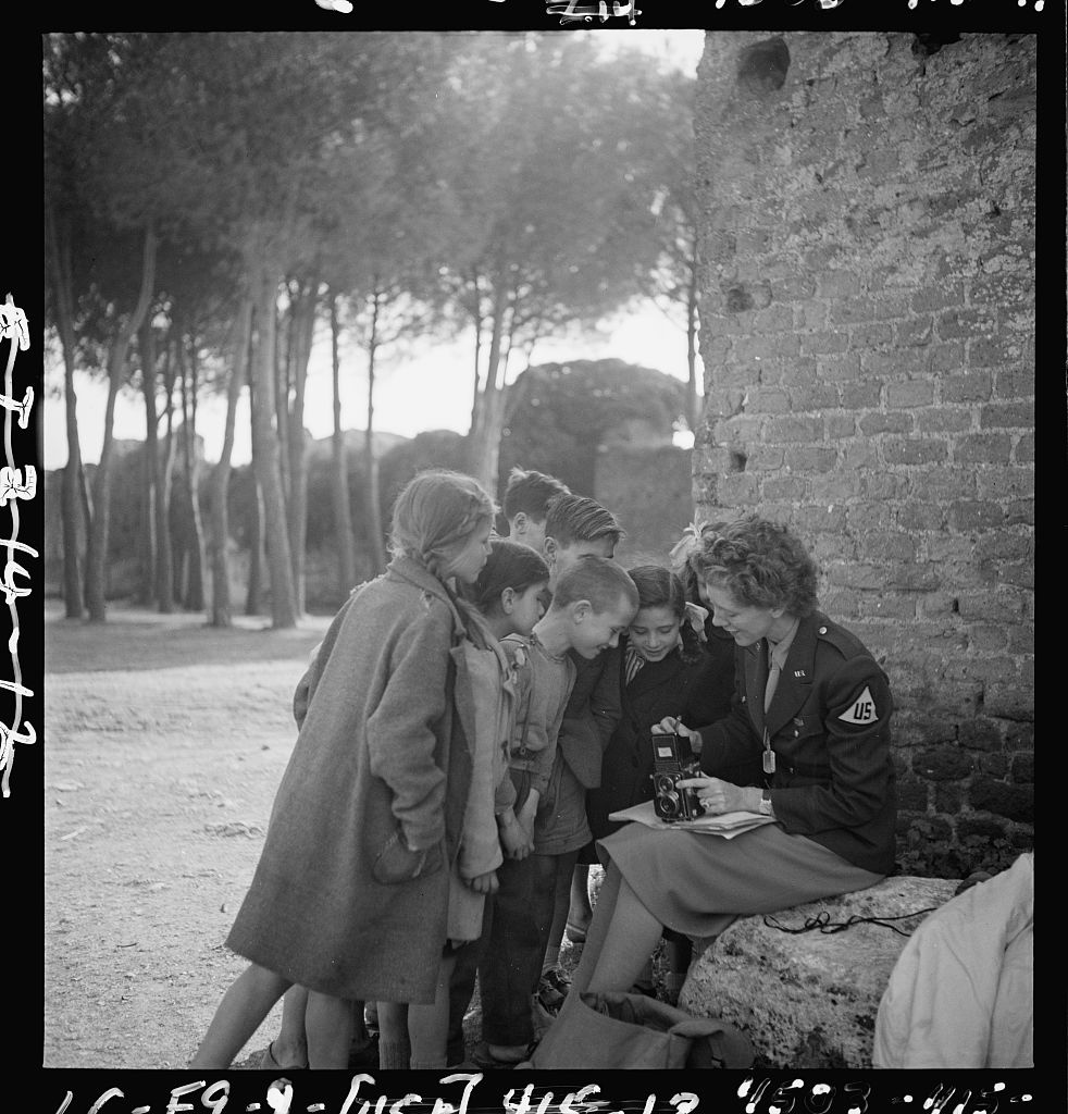 Imager description: Toni Frissell holds a camera on her lap while several children stand around her. This photograph was taken somewhere in Europe during 1945. Photo from the Library of Congress, Prints and Photographs Division.