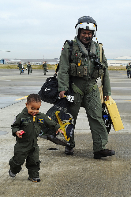 Image description: Lt. Cmdr. Chris Singletary walks with his son during a homecoming celebration at the Naval Air Facility in Japan. Photo by Mass Communication Specialist 2nd Class Justin Smelley, U.S. Navy.