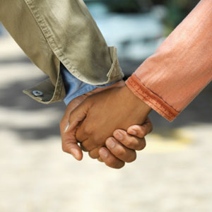 Photograph of two young people holding hands.