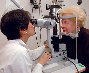 Lady doctor examining an eldarly woman's eye.
