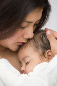 Photograph of a teen mother cuddling her infant.