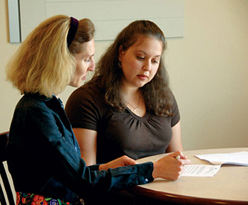 Two ladies talking over a document.