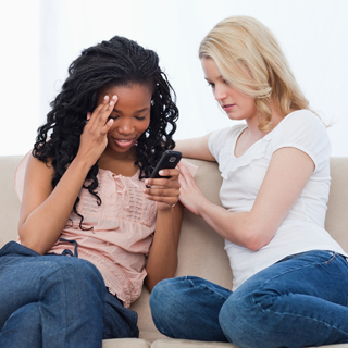 Two women sitting on a couch.  Upset woman is being comforted by the other woman.